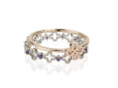 Un anillo dorado con cristales transparentes y un anillo plateado con cristales morados
