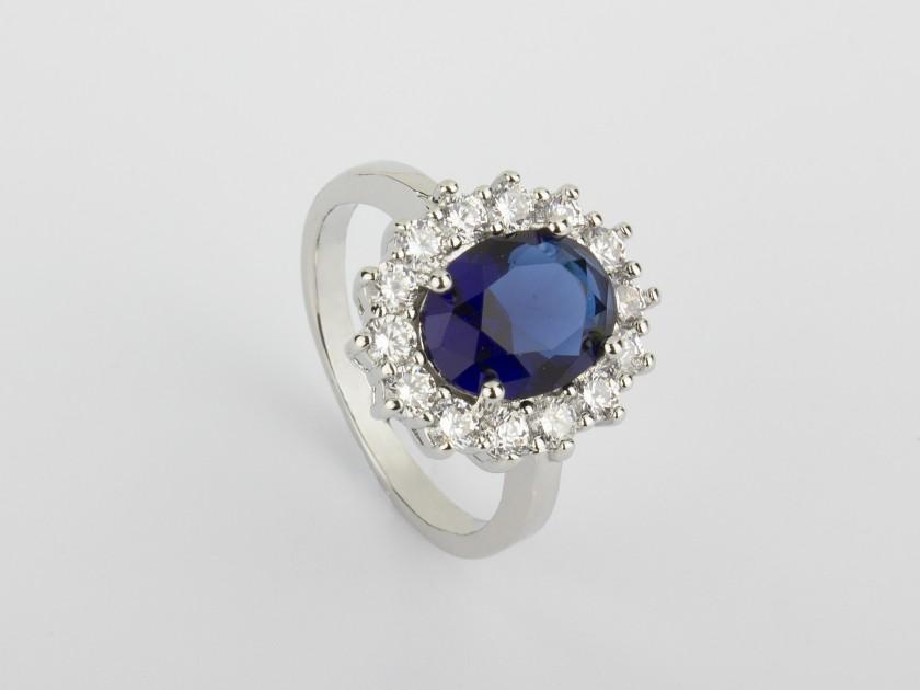 Anillo plateado engastado con cristales transparentes y un cristal azul zafiro