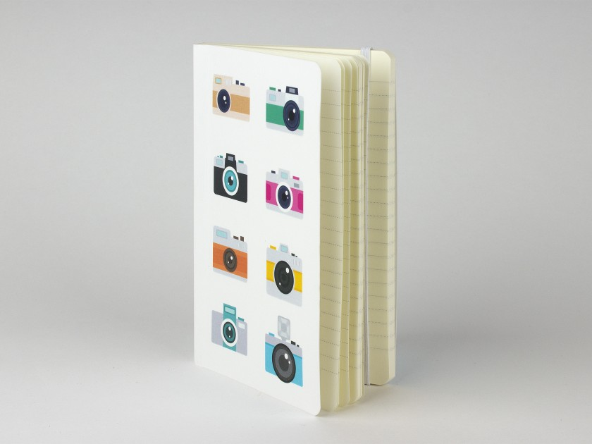 notebook standing upright showing an illustrated cover with several coloured cameras.