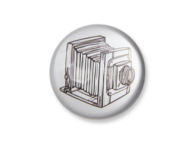 glass paperweight seen from above with an illustration of an old camera inside