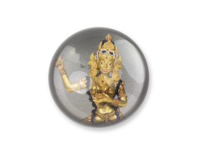Paperweight seen from above with the image of a statuette of the Buddhist goddess Vajravârâhî.