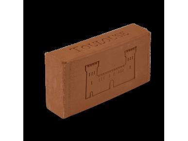 brique posée sur la tranche avec une silhouette du Castelet gravée sur une face de la brique