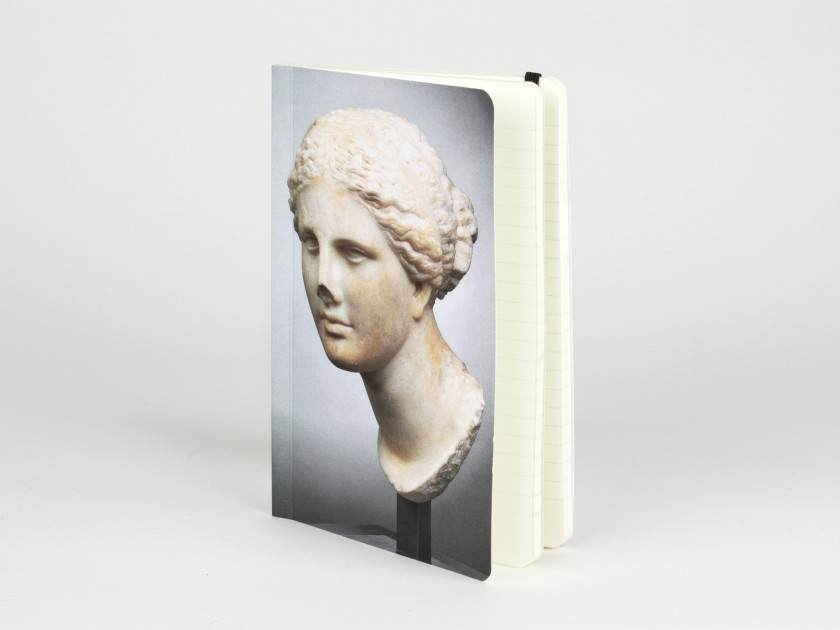 Cuaderno visto de frente con la cabeza de una estatua de Venus impresa en la tapa