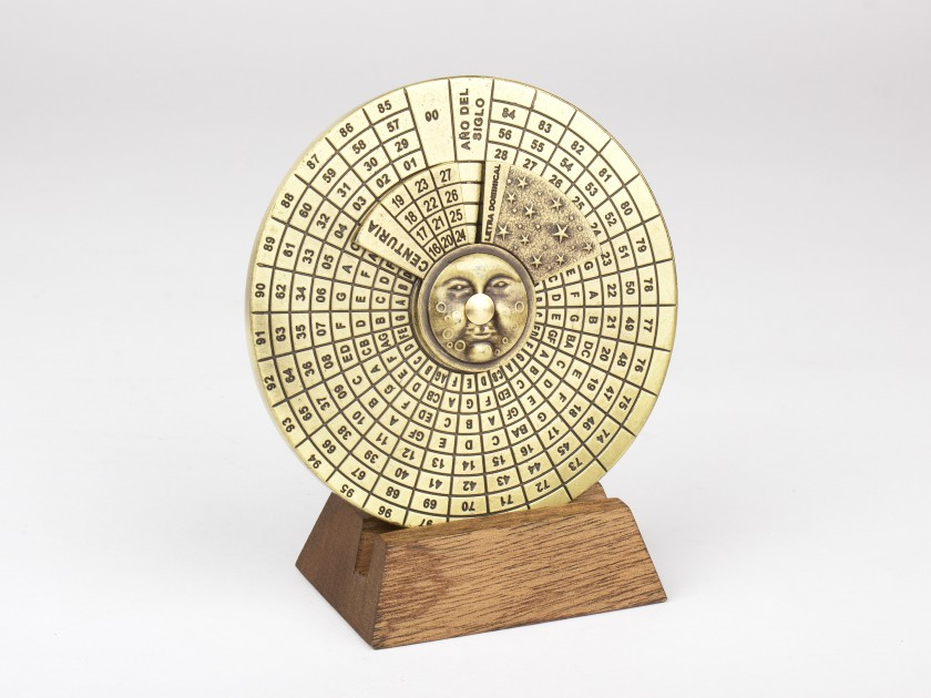 Perpetual calendar in gilded metal on a wooden base