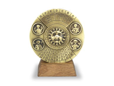 Calendrier perpétuel en métal doré posé sur un socle en bois