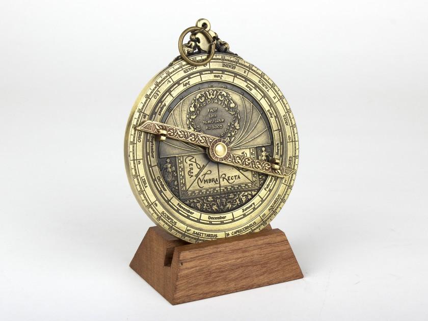 Astrolabio planisférico de metal dorado sobre base de madera