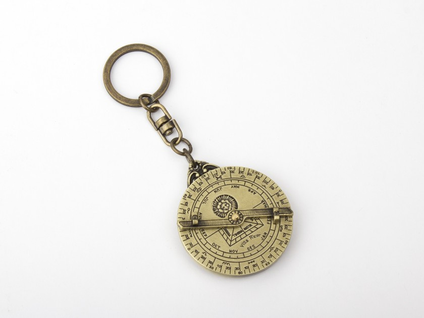 llavero de metal dorado que representa un mini astrolabio