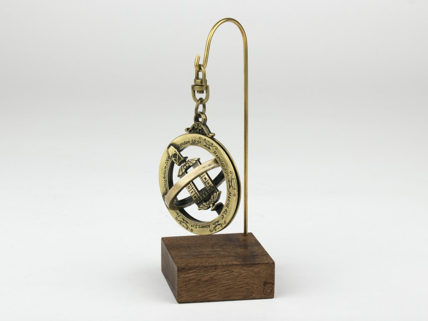 gilded metal astronomical ring on a wooden base