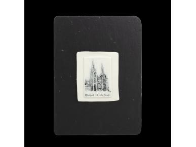 plaça de porcellana decorada amb una il·lustració de la catedral de burgos, situada sobre una pissarra