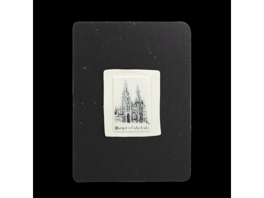 cuadrado de porcelana decorado con una ilustración de la catedral de Burgos, colocado sobre una pizarra