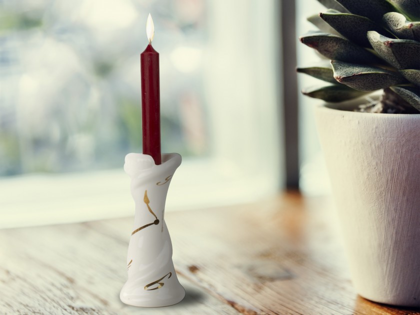 White and gold enamelled ceramic candlestick with a candle